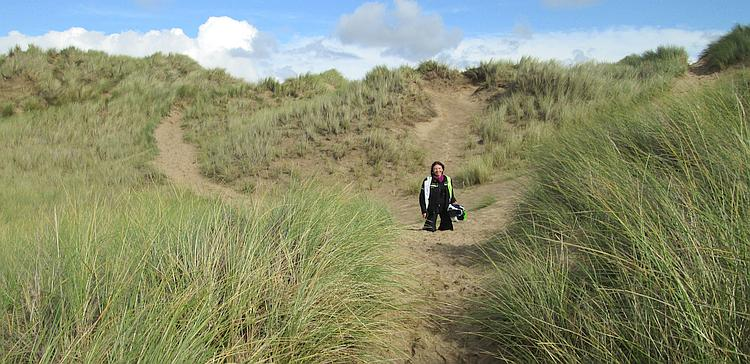 Sharon's on her knees in the sandy dunes as we head to the beach