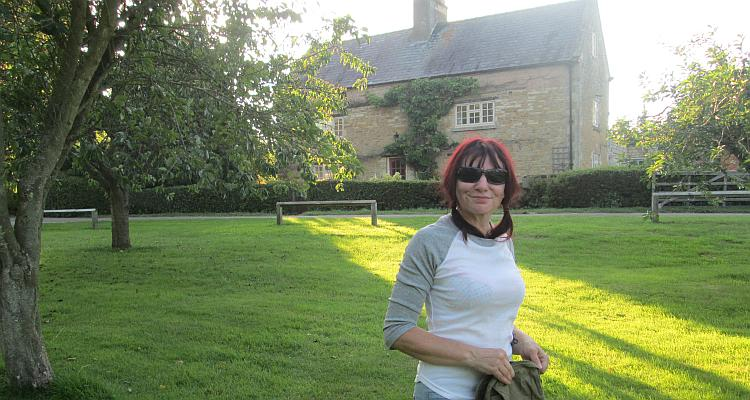 Sharon smiles wearing her sunglasses with a stone farmhouse behind her at the campsite