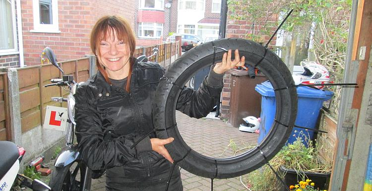 Sharon holds a motorcycle tyre with zip ties around it
