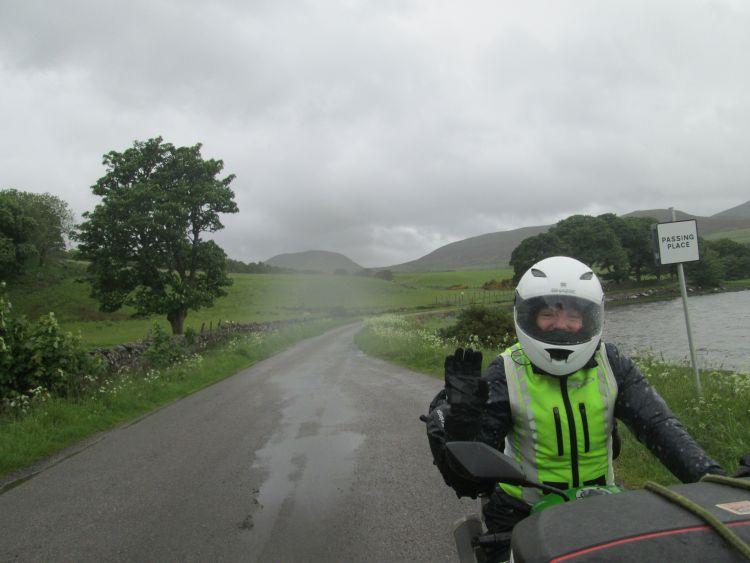 Sharon waves at the camera from her bike in dark skies and rain falls all around