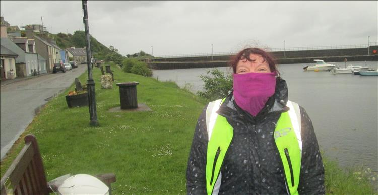 Sharon has her scarf over most of her face in the heavy rain at Helmsdale