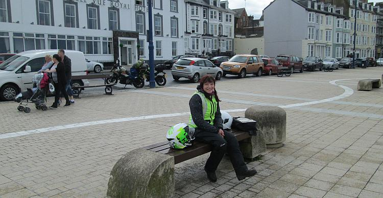 Sharon sat on a bench smiling with a large white seafront hotel behind her