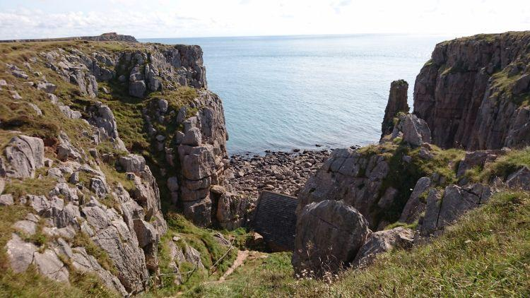 Between craggy rocky cliffs we can see the sea and the roof of a very small building