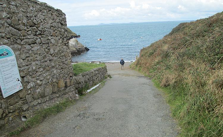 A steep narrow lane leads down to a tiny patch of shingle beach
