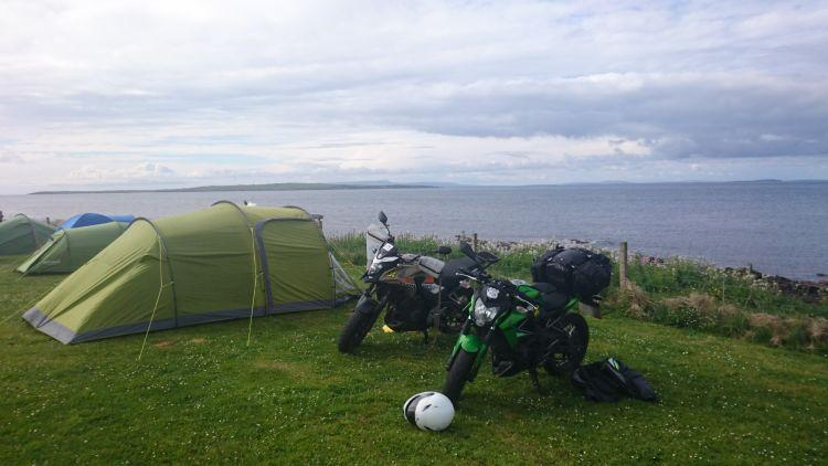 The tent and the 2 motorcycles pitched up at the campsite with the North Sea behind