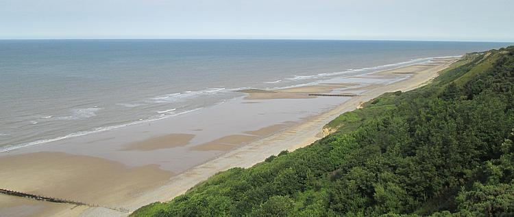 Small waves lap the sandy beach at Cromer, down below the bluffs