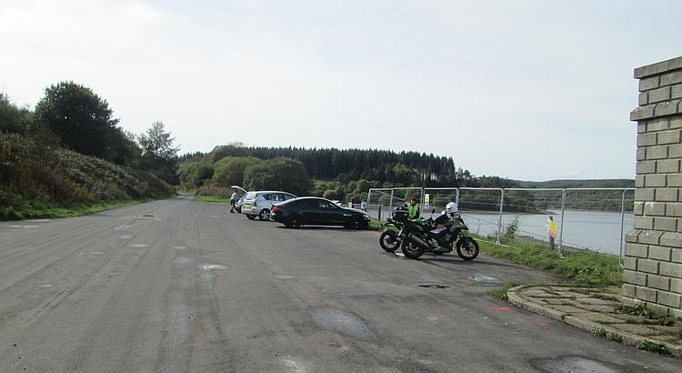 A broad car park, quiet among the hills and next to the reservoir