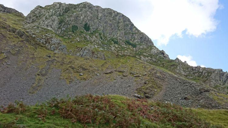 A large rocky outcrop forming a cliff atop a hill in mid wales