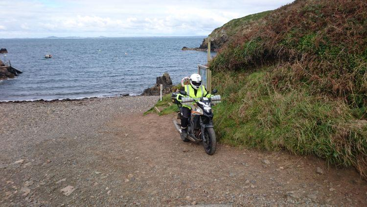 Ren on his motorcycle are facing inland now on a tiny shingle beach after turning around