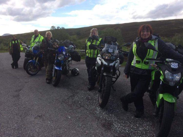 5 riders stand by their machines on a Highland road, all smiling at the camera