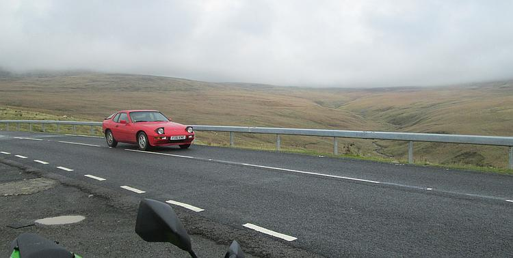 An old red Porsche crosses the misty moors and hills of the pass, quite safely