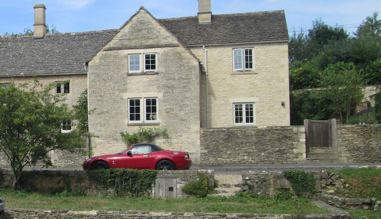 A large stone house with a sports car outside