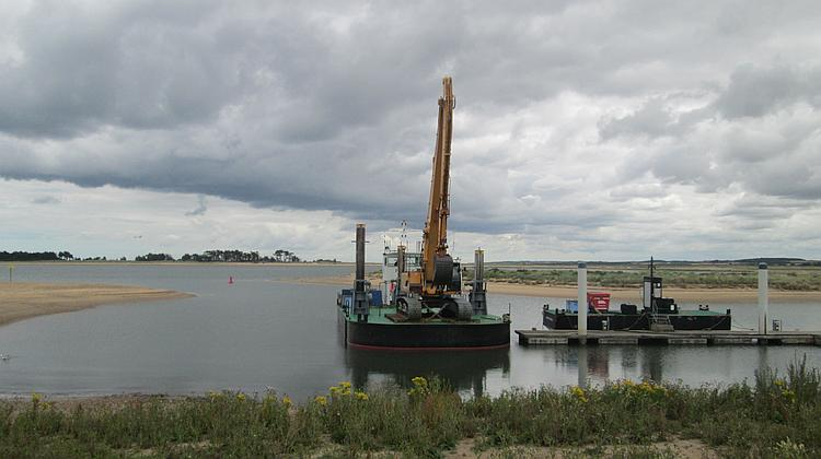 A large tracked excavator on a barge at Wells-next-the-sea.