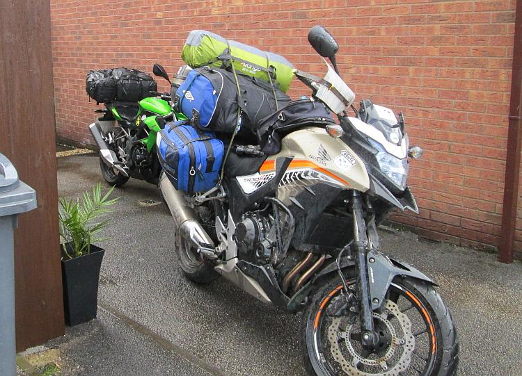 The 2 motorcycles buckling under a mound of luggage, ready for the forthcoming adventure