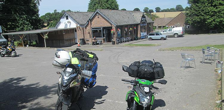 Loomies cafe, a brick building, a car park and some motorcycles in the sunshine