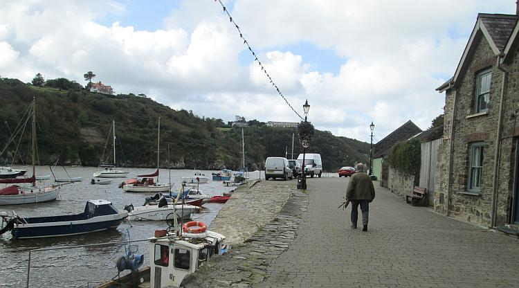 The windswept harbour of Lower town Fishguard. Boats, hills, walls and houses