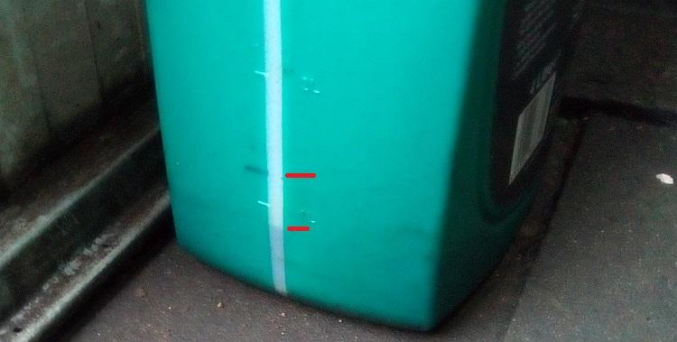 The marked level and the current level visible on the side of the oil container