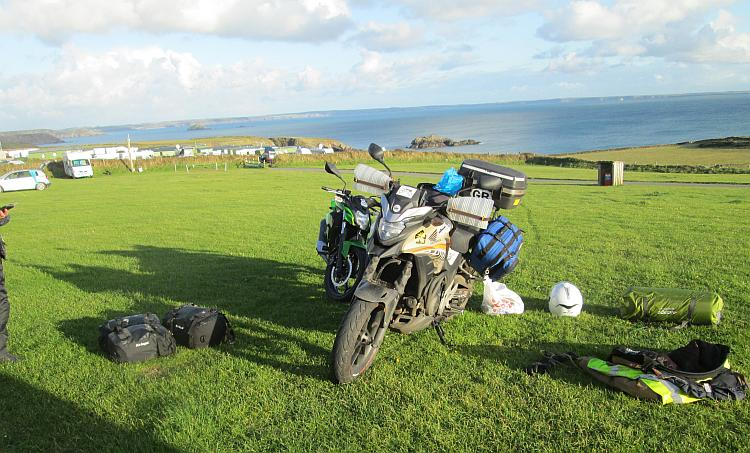 The motorcycles and the camping kit spread out with the vast bay behind