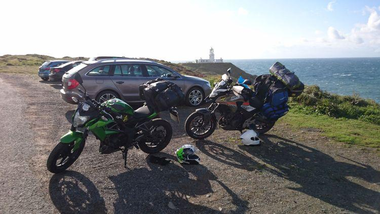 Strumble Head lighthouse is in the distance with the motorcycles and some parked cars in front