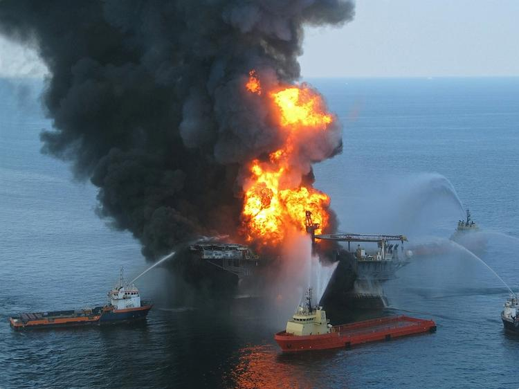 stock photo of a massive oil fire on a rig with ships trying to put it out