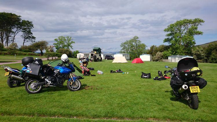 Motorcycles are having tents and gear fixed onto them in the sun at the campsite in Applecross