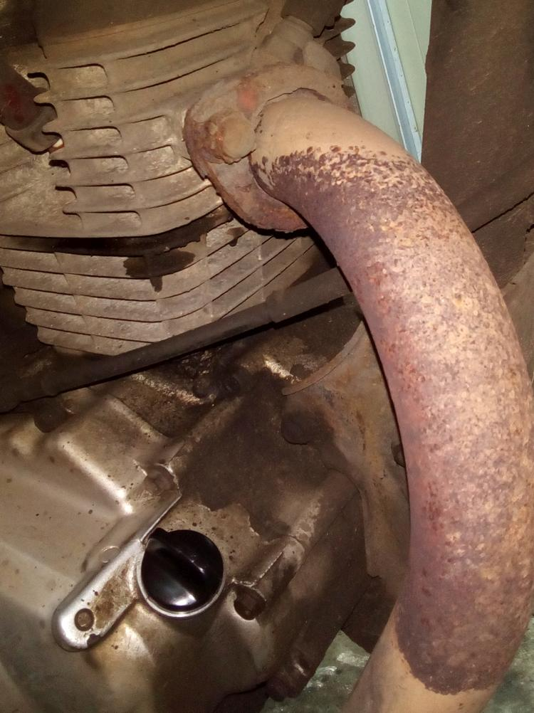 The corroded aluminium and rusty exhaust of Ren's CBF125
