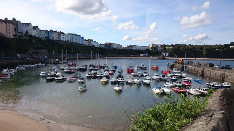 Small boats fill the curved harbour in sun filled Tenby