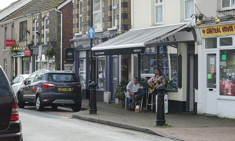 A couple play guitar and sing outside a small shop at Ystradgynlais