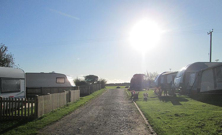 Bright low sunshine over caravans and blue skies at the camp site