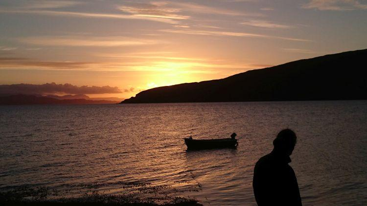 A deep orange sunset, a loch, a small boat and a person in outline at Ullapool