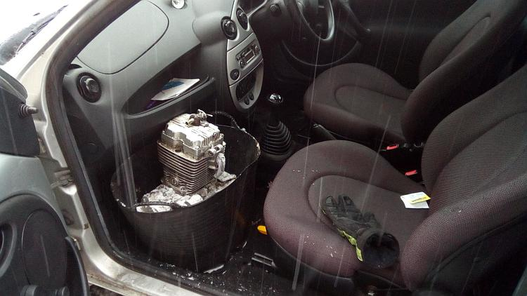 The engine in the bucket is now in the footwell of Ren's car while the snow is falling