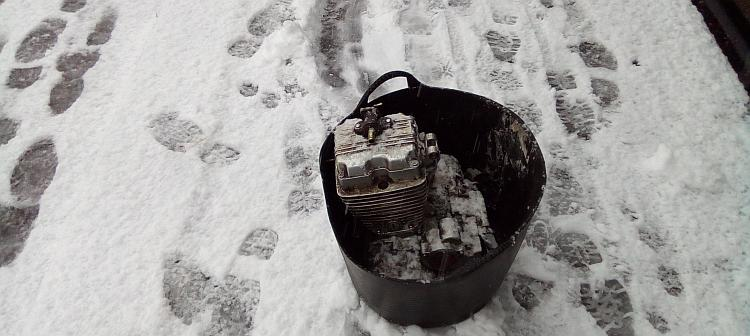 The 125 engine is in a black rubber bucket on a snow covered footpath