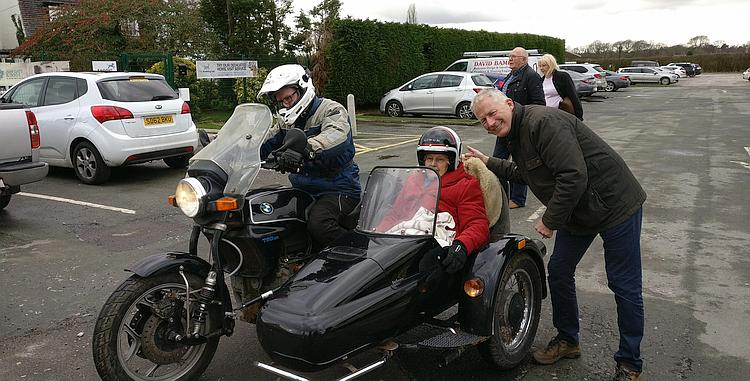 Annie is swaddled in the sidecar with Phil riding and David beside her