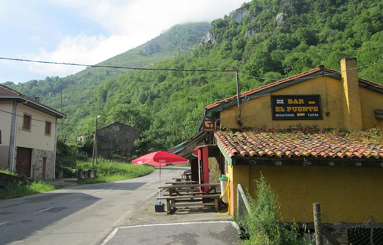 A light brown Spanish bar with vast steep tree covered hills in the background at Puente de Vega