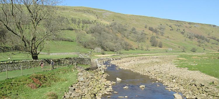 A small river flows through boulders, rolling green hills and glorious blue skies at Swaledale