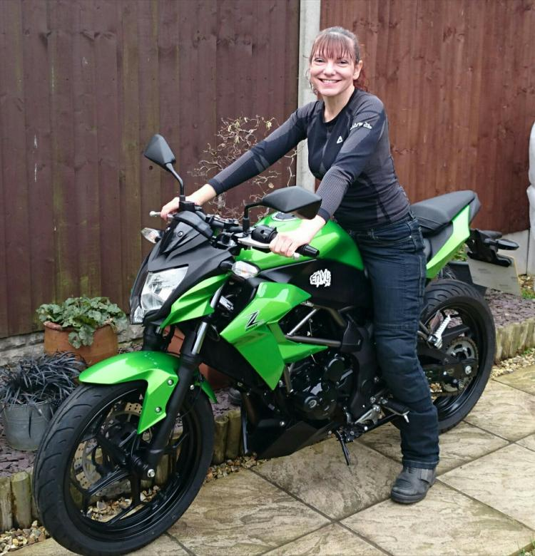 Sharon is sat on her Kawasaki Z250SL smiling and happy