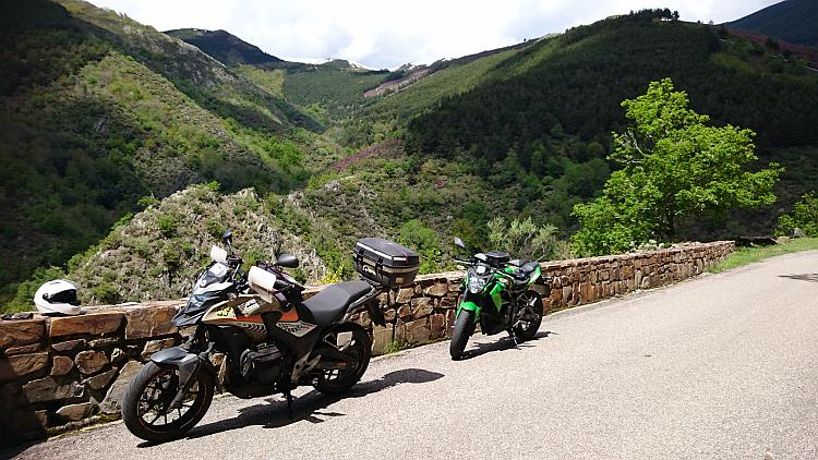 The Honda and the Kawasaki on a mountainside road overlooking dramatic angular mountains