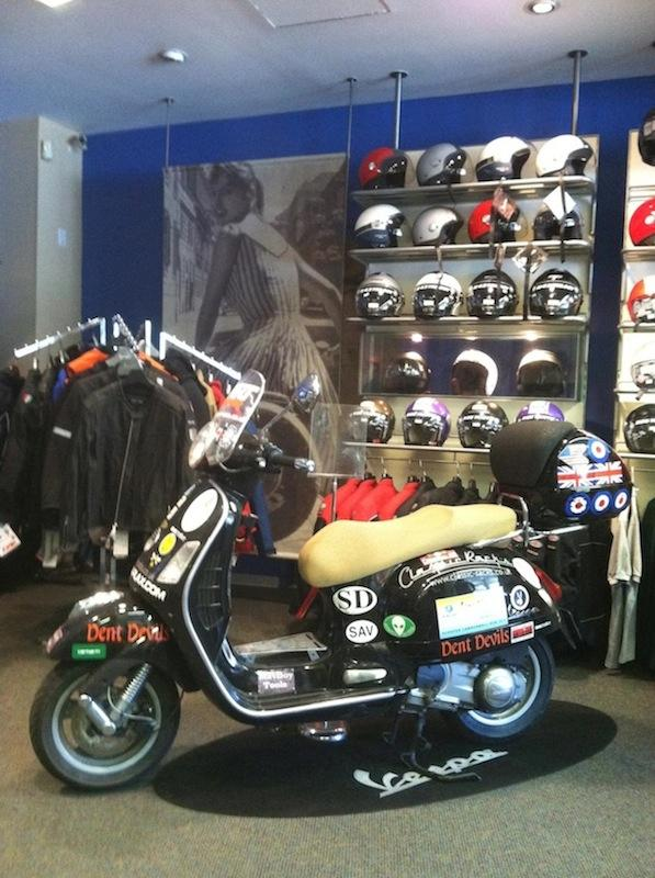 A Vespa scooter covered in sponsor stickers at the shop