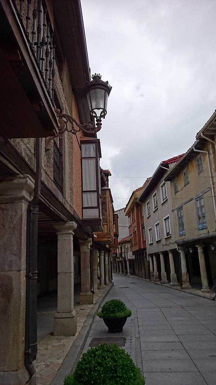 The narrow lane of the town and the buildings hang overhead
