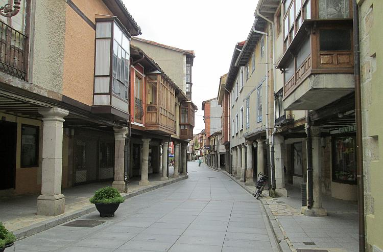 A narrow street with the houses and shops almost overhanging into the lane