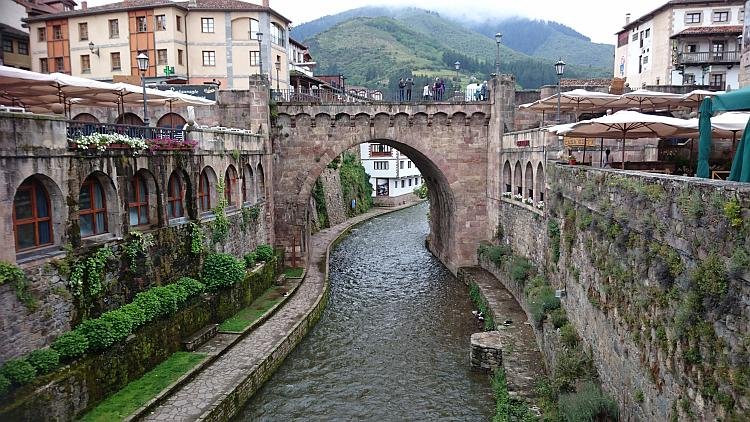 An old ornate stone bridge crosses a river cut deep between the houses and verandas in Potes