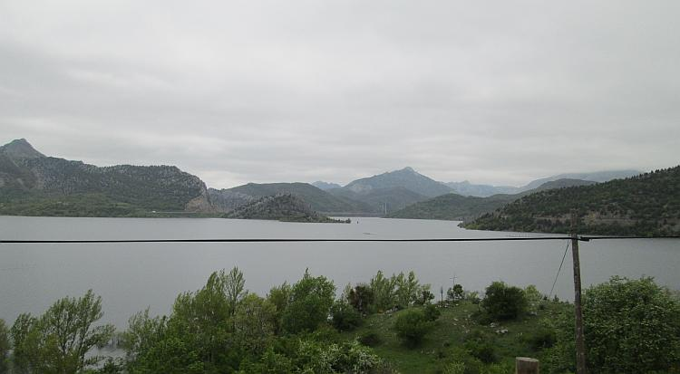 Looking across the reservoir we see endless mountains stretching out to the grey skies