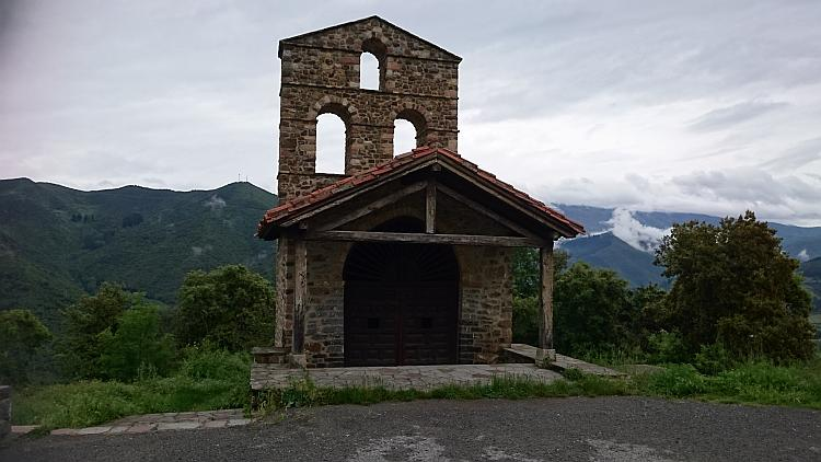 Side view of the tiny chapel with the Picos mountains behind