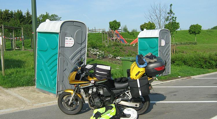 2 portaloos and a car park with a playground, a French service stop