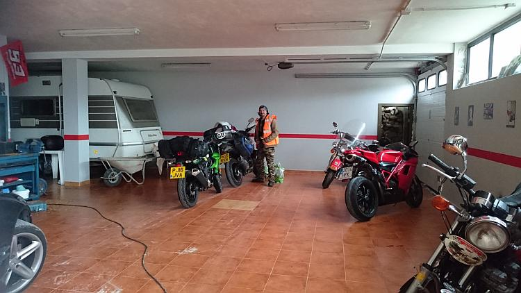 Inside is a large garage with a caravan, several motorcycles and a lot of space