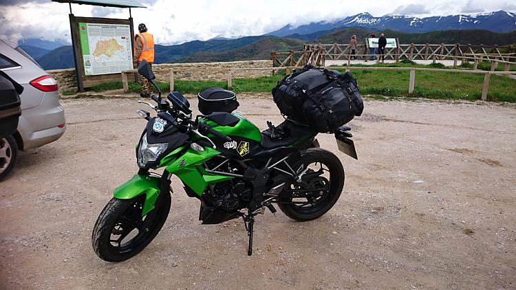 Sharon's 250 with a tourist information board behind then the vast mountains stretch away