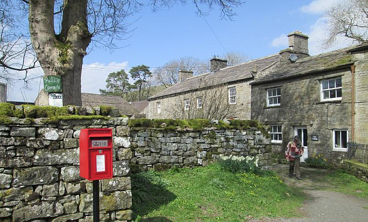 A stone farmhouse, trees and sunshine in the village of Keld