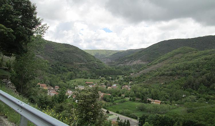 A village is deep down in the valley surrounded by steep hillsides in Northern Spain