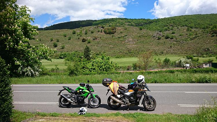 The 250 and 500 parked by the side of the road surrounded by the lush verdant scene