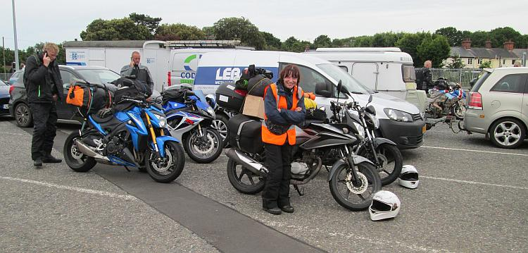 Sharon is smiling at the camera with motorcycles and cars in the queue for a ferry behind her